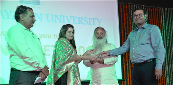 Chairman of the board of governance giving the memento to poet-writer Khushboo Sharma