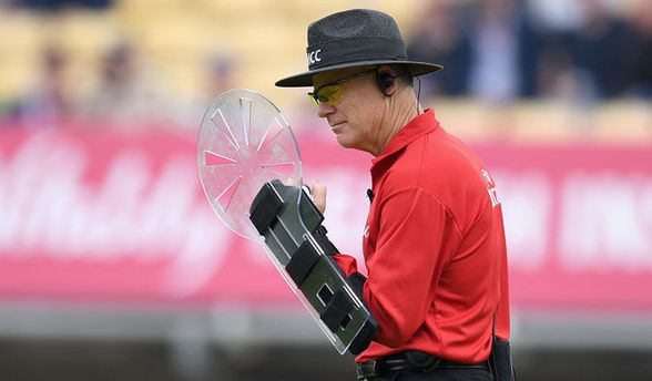 Protective shield in hand of umpire